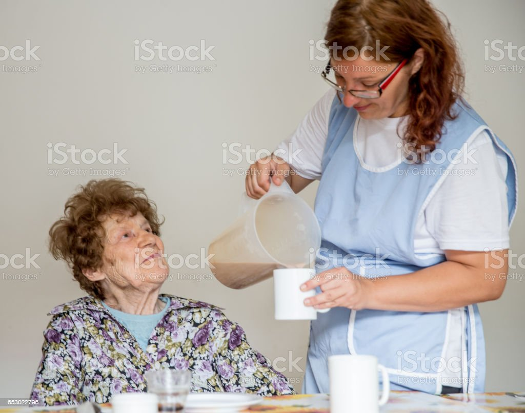 Nurse At The Care Center Serving Breakfast To The Resident stock photo