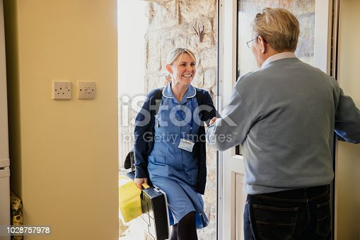 istock Nurse at the Door Making a House Call to a Senior Man 1028757978