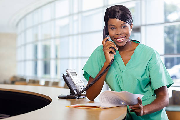 nurse at work station - nurse on phone stock photos and pictures