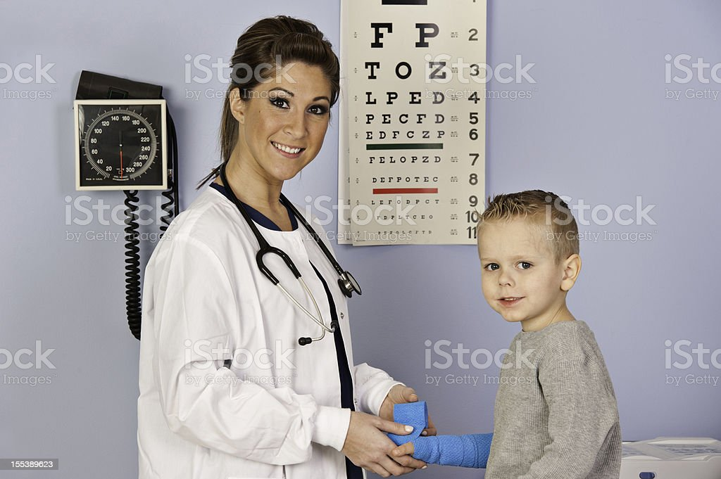 Nurse bandaging a little boys arm. royalty-free stock photo