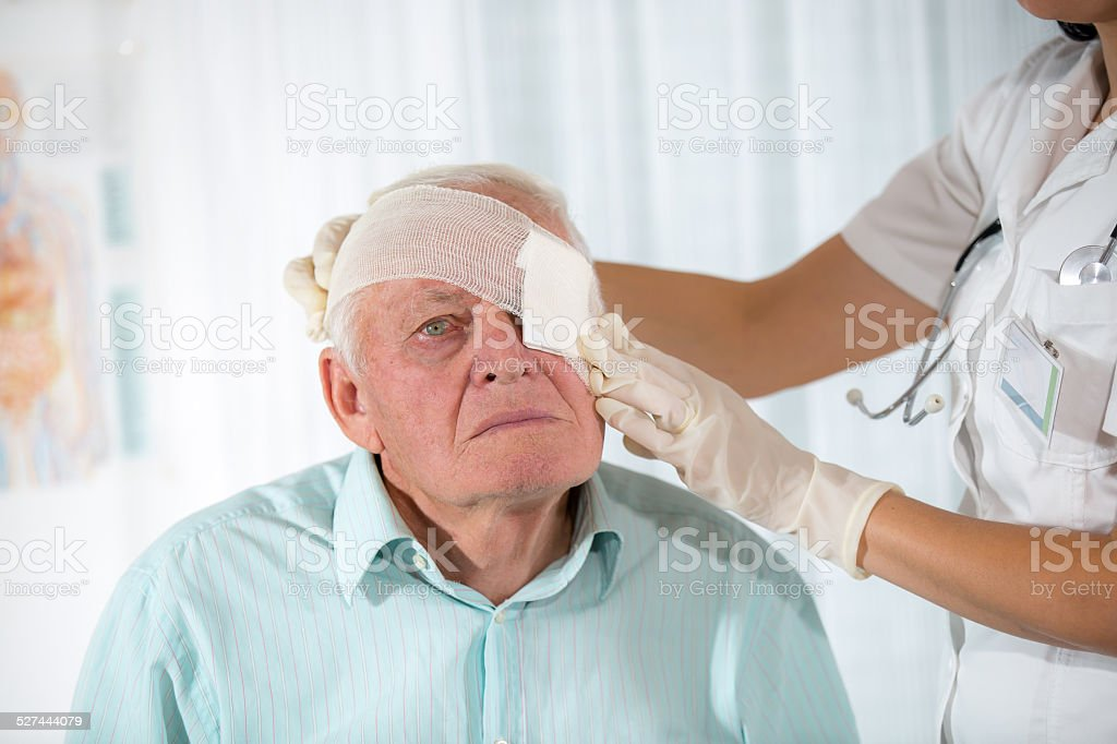 Nurse bandaging eye an older man stock photo