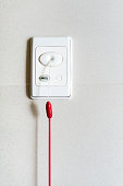 Nurse call switch with emergency pull cord isolated on white wall in patient room. A communication equipment for emergency or asking for help.