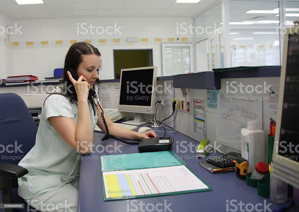 Nurse calling on phone in ICU stock photo