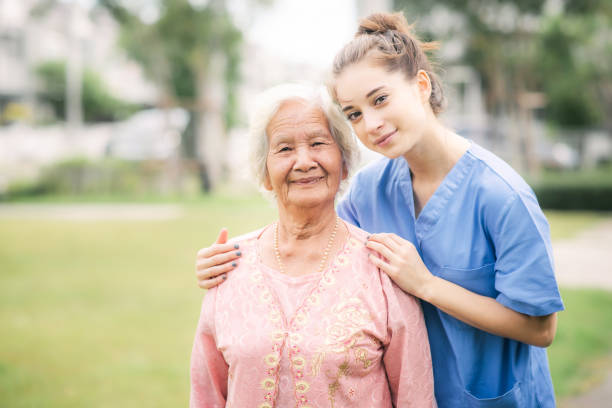 nurse caregiver with Asian elderly woman stock photo
