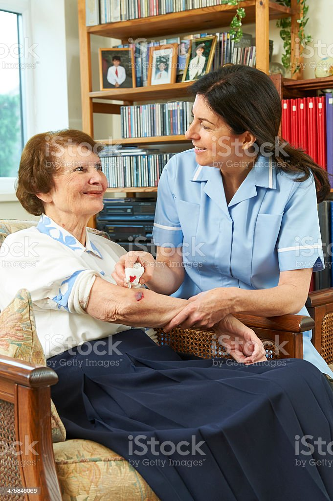 Nurse caring for senior smiling at each other stock photo