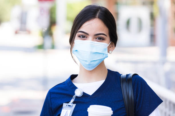 Nurse carrying coffee and wearing protective mask poses for photo stock photo