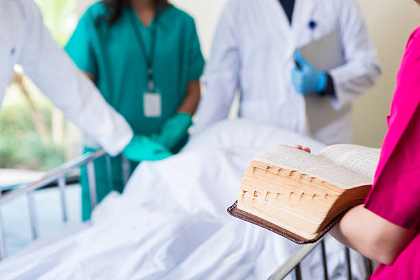 Nurse chaplain reading Bible in hospital room of deceased patient Nurse chaplain reading Bible in hospital room of deceased patient clergy stock pictures, royalty-free photos & images