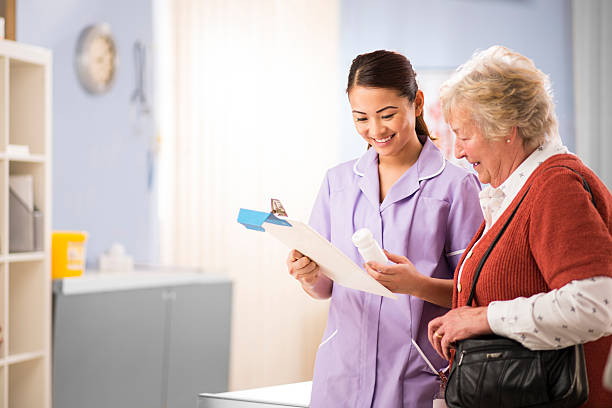 nurse chats to senior patient a young nurse stands and chats to a senior woman patient as she leaves the surgery. She is wearing a lilac nursing uniform and holding a bottle of pills . She is smiling to the senior woman and explaining . In the background a hospital interior can be seen. outpatient stock pictures, royalty-free photos & images