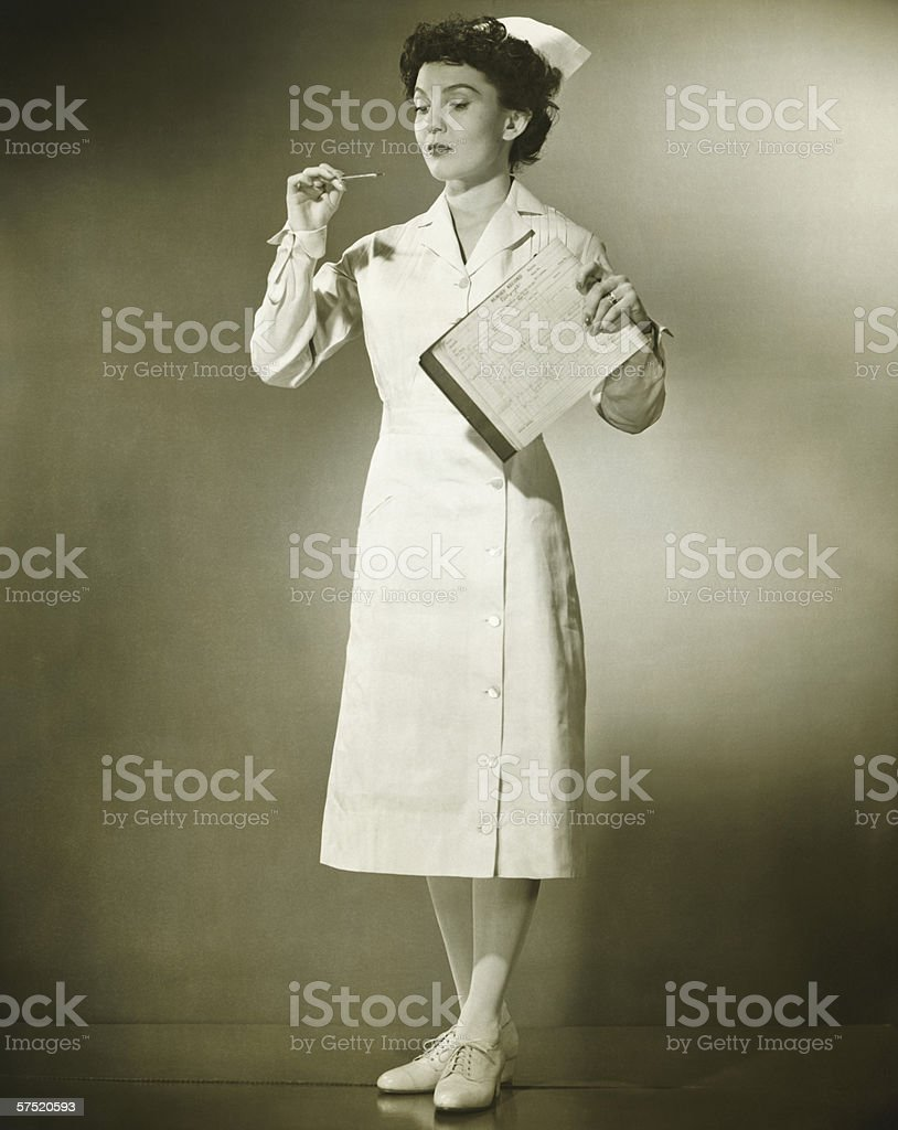 Nurse checking at thermometer in studio, (B&W) royalty-free stock photo