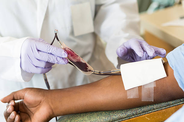 nurse checking bag of blood while patient gives donation - blood donation stock pictures, royalty-free photos & images