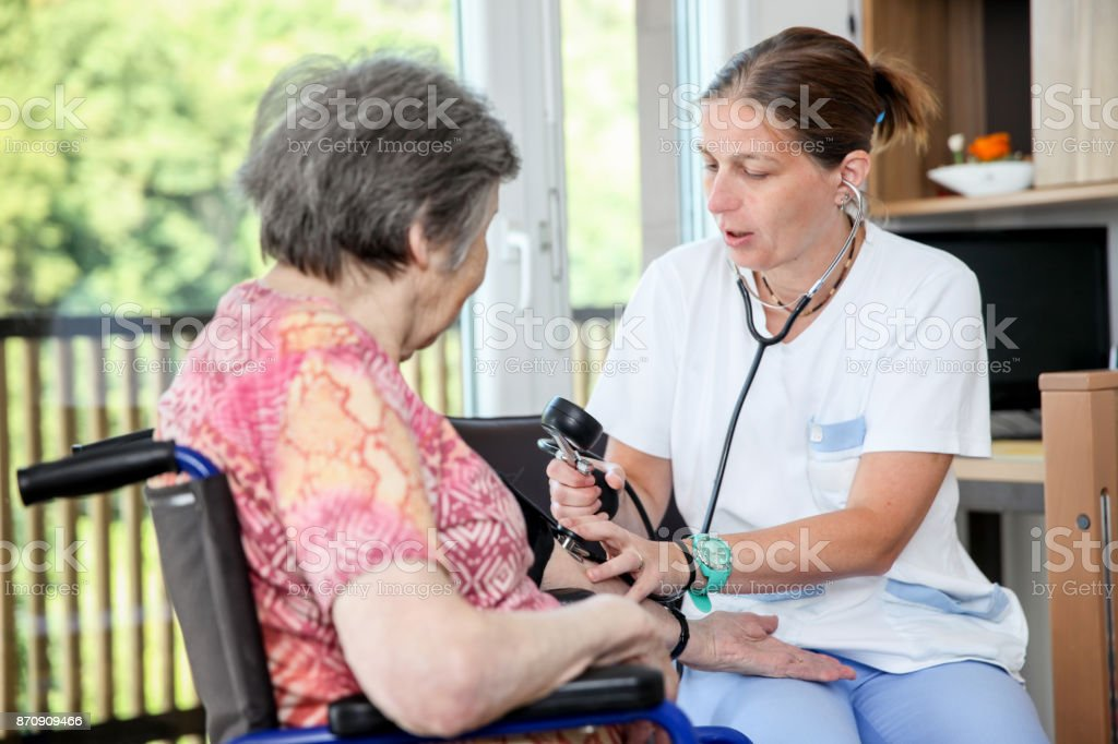 Nurse Checking Blood Pressure of Senior Female Patient stock photo