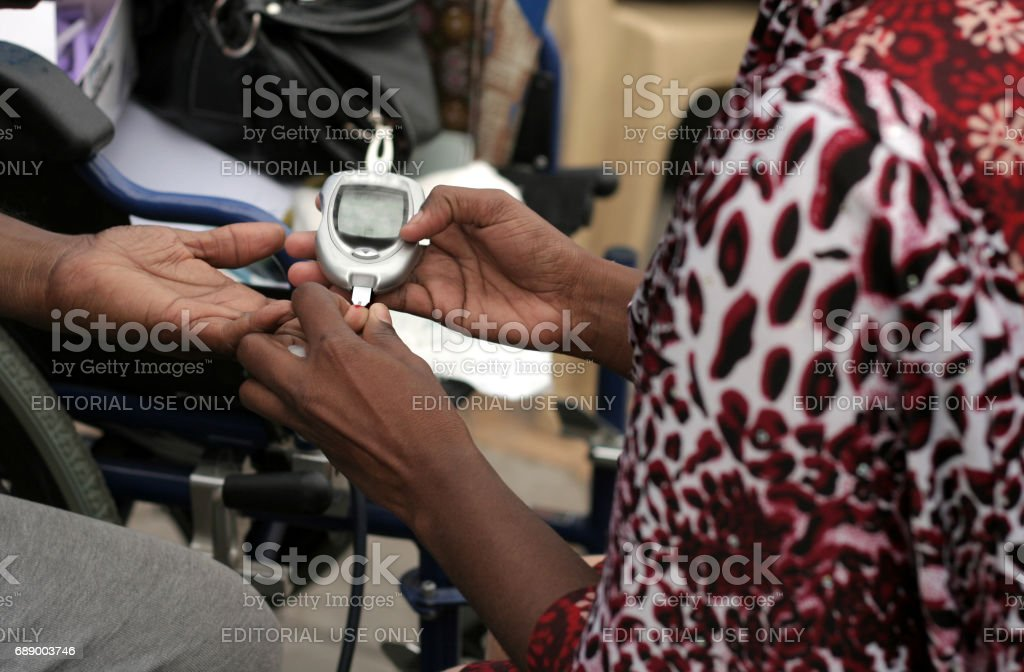 Nurse checking Blood sugar level of woman in a medical camp during happy roads program(vehicular Traffic stopped) in necklace road,Hyderabad,India. stock photo