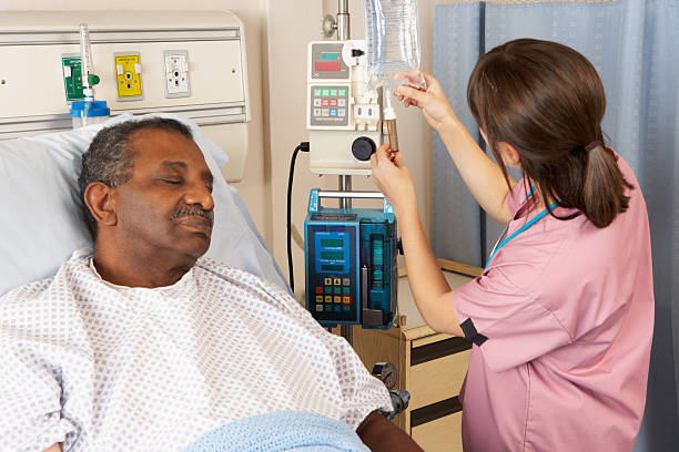 Nurse Checking Senior Male Patient's IV Drip On Ward stok fotoğrafı