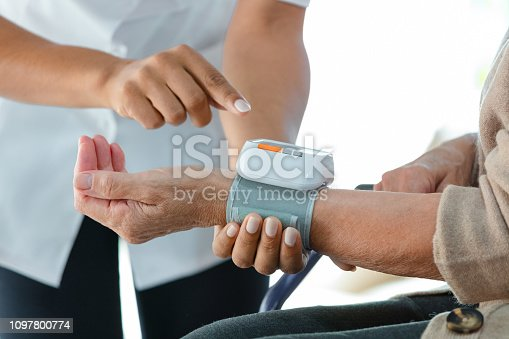 Home nurse measuring the arterial pressure of the senior woman. Close up of hands, unrecognizable people.