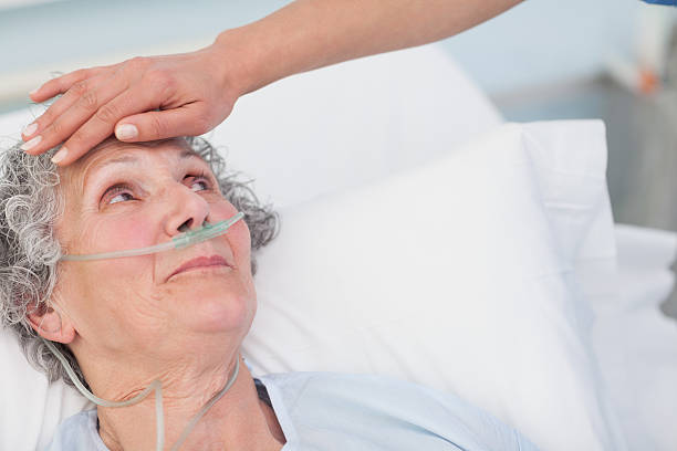 Nurse checking the forehead of older female patient in bed Nurse touching the forehead of a patient in hospital ward medical oxygen equipment stock pictures, royalty-free photos & images