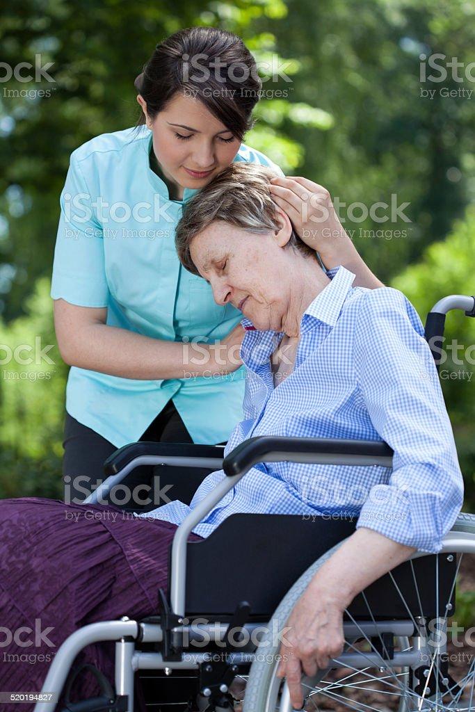 Nurse comforting an old woman on wheelchair stock photo