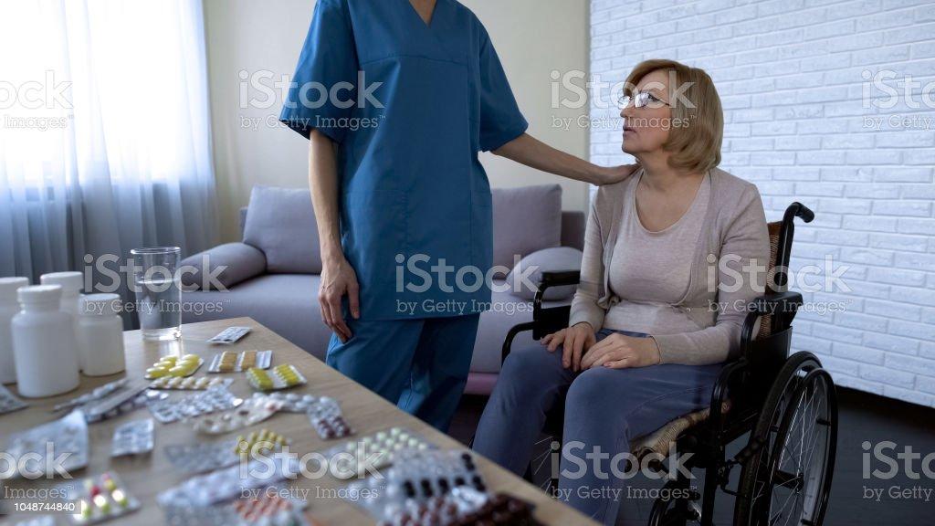 Nurse comforting tired female patient in wheelchair, nursing home,...