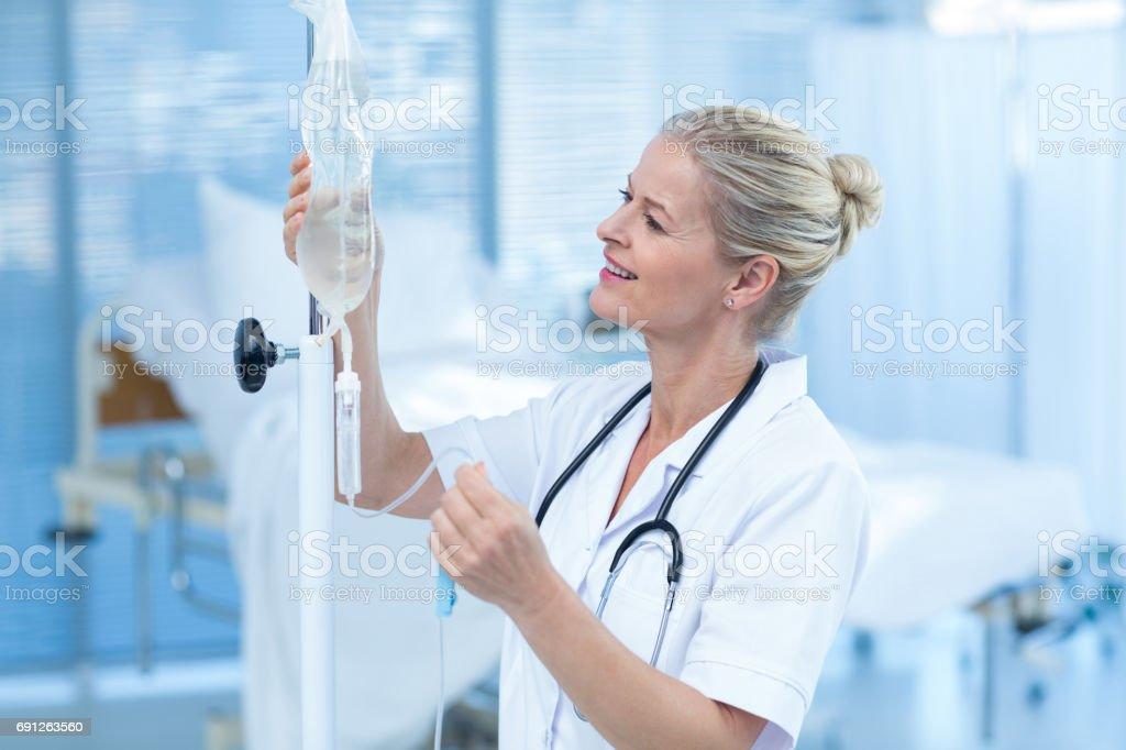 Nurse connecting an intravenous drip stock photo