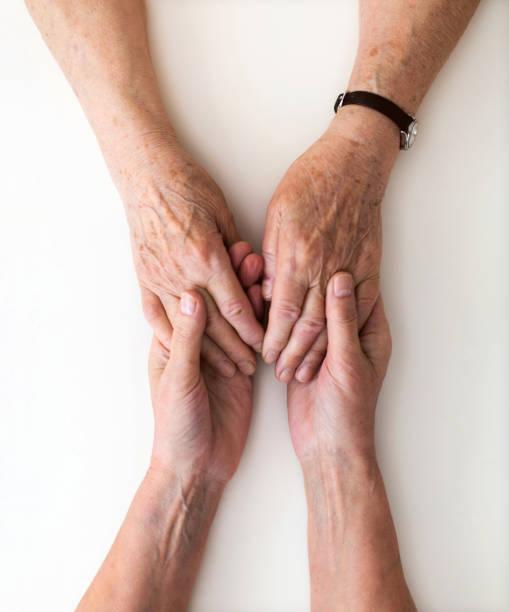 Krankenschwester tröstet ihre ältere Patientin, indem sie die Hände hält – Foto