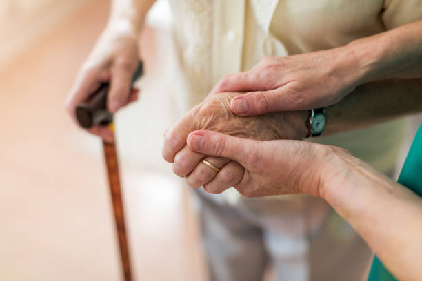 Nurse consoling her elderly patient by holding her hands Nurse consoling her elderly patient by holding her hands aging stock pictures, royalty-free photos & images