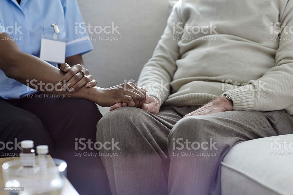 Assisted living - Home healthcare nurse consoling elder man. Female...