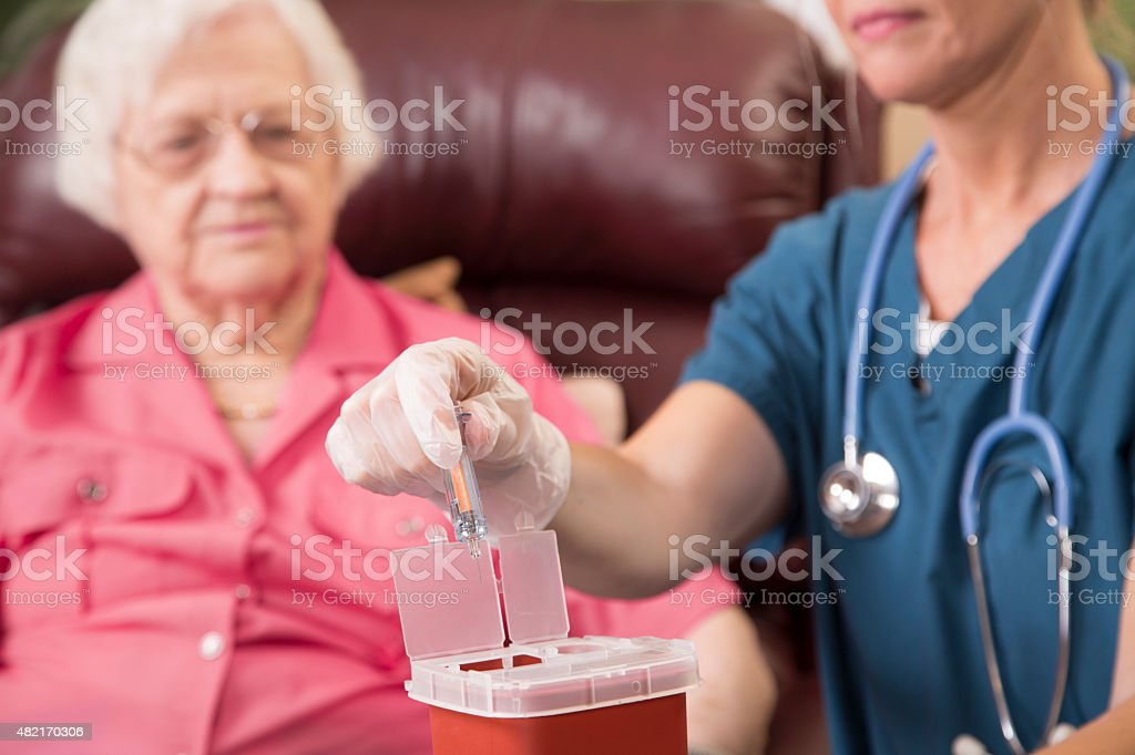 Nurse demonstrating proper disposal of medications, syringes. stock photo