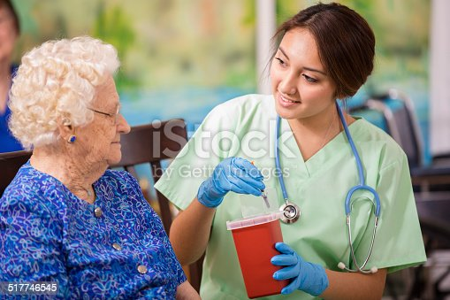 Latin descent female nurse or doctor demonstrates proper disposal technique of 'sharps' medications to elderly female patients.  Home or clinic setting.  Woman is over 100 years old.