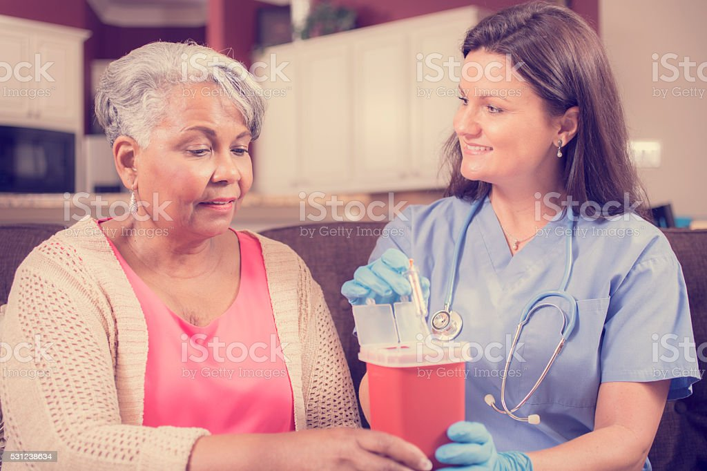 Nurse demonstrating proper disposal of syringes. stock photo