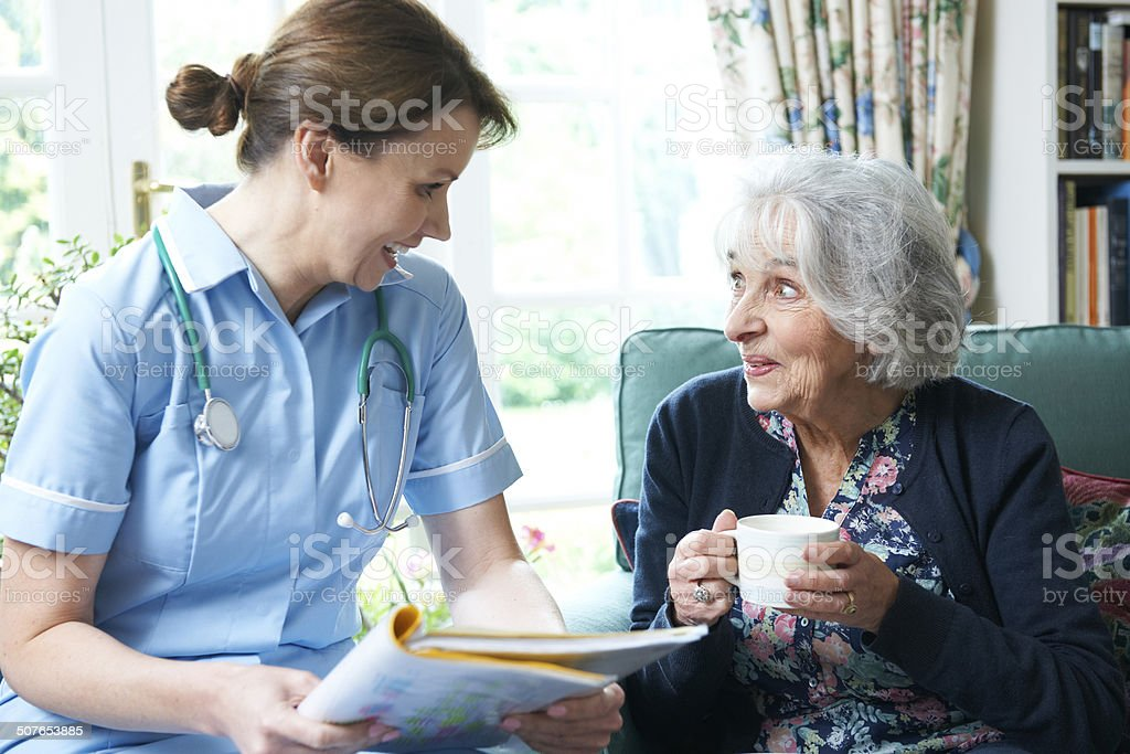 Nurse Discussing Medical Notes With Senior Woman At Home stock photo