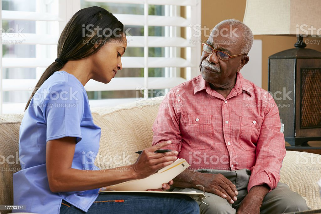 Nurse Discussing Records With Senior Female Patient During Home stock photo