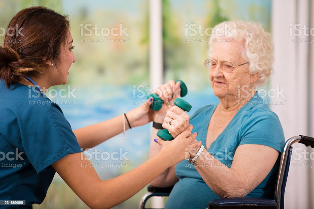 Nurse does physical therapy with senior woman patient. Arm strengthening. stock photo