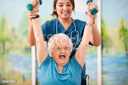istock Nurse does physical therapy with senior woman patient. Arm strengthening. 534972501