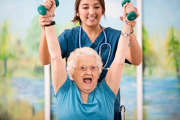 enfermera ¿fisioterapia con mujer mayor paciente. brazo de resistencia. - geriatría fotografías e imágenes de stock