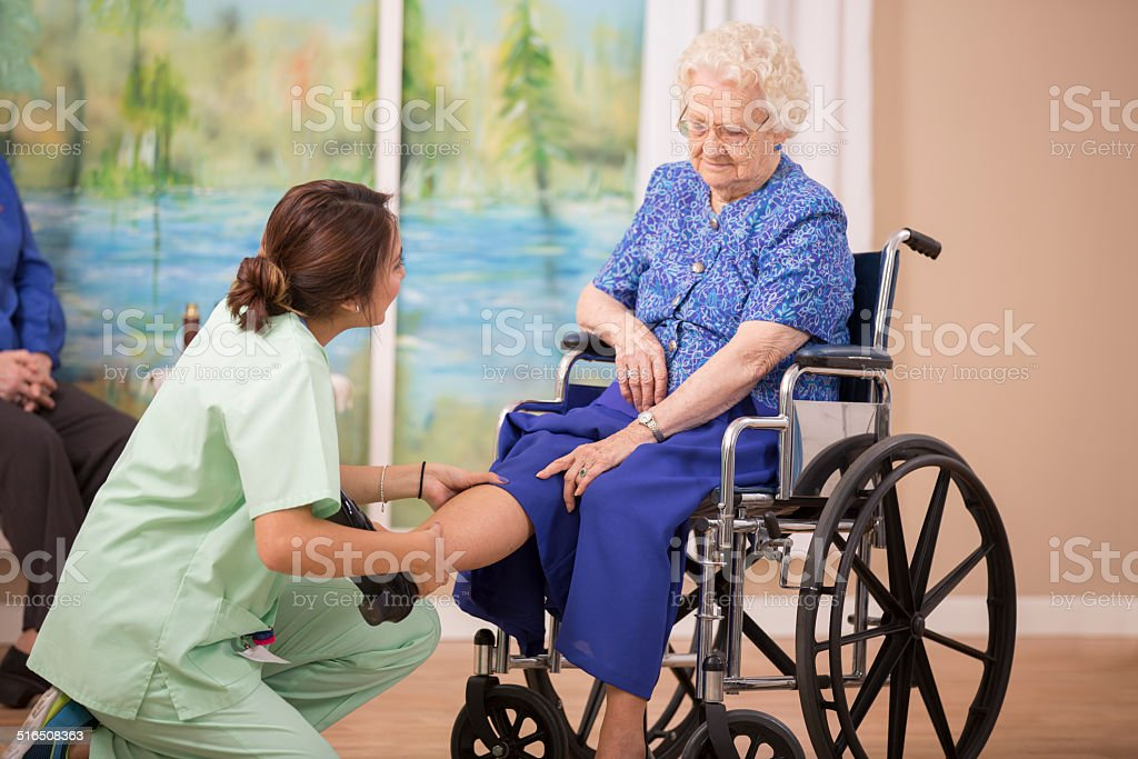 Nurse does physical therapy with senior woman patient. Leg strengthening. stock photo