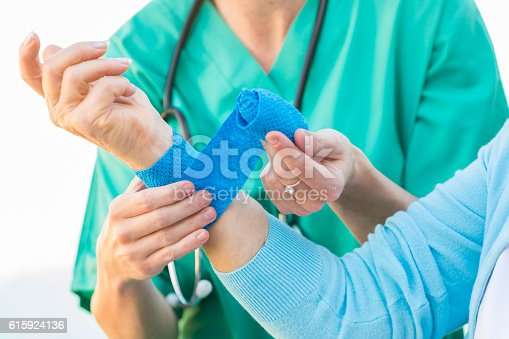 istock Nurse dressing a wound of an injured senior adult 615924136
