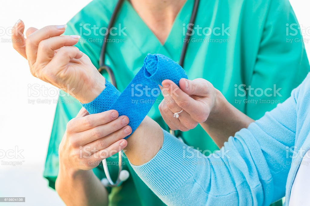 Nurse dressing a wound of an injured senior adult stock photo