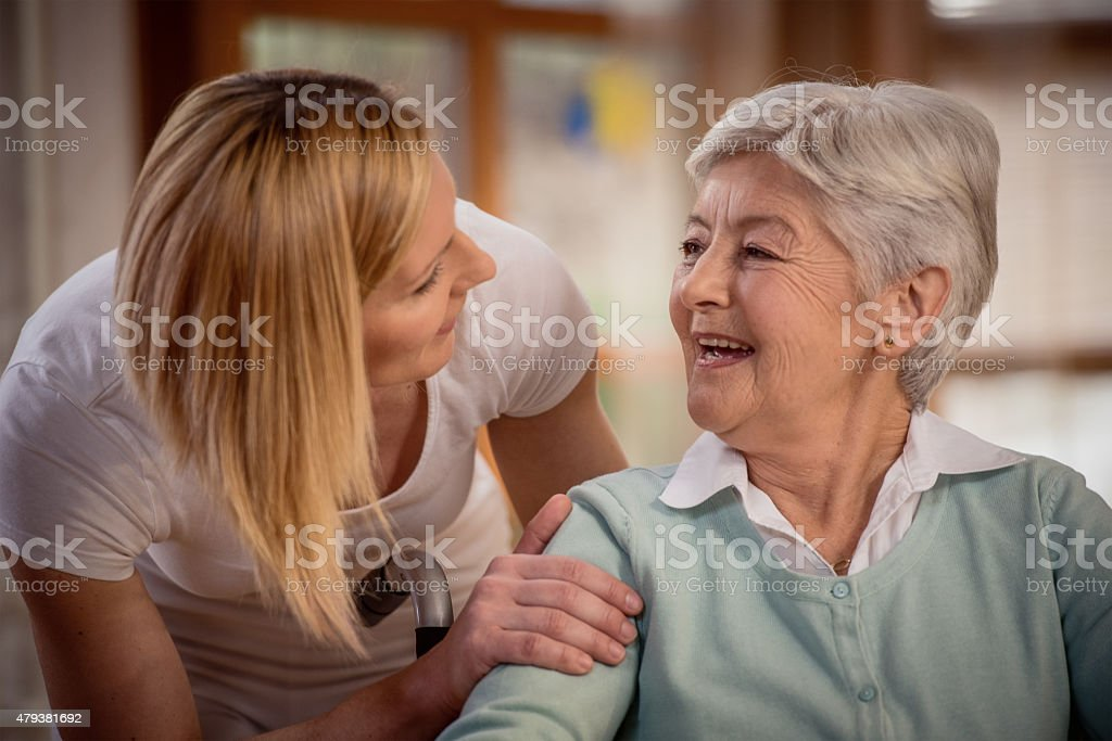 Nurse during home visit with senior woman stock photo