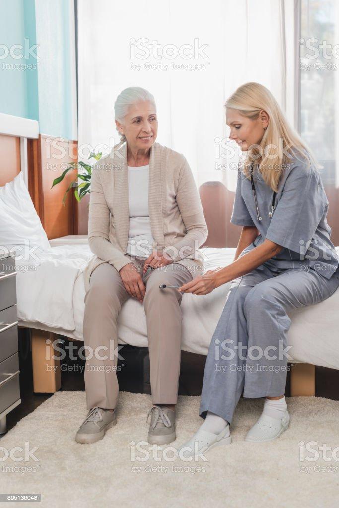 nurse examining patient with reflex hammer stock photo