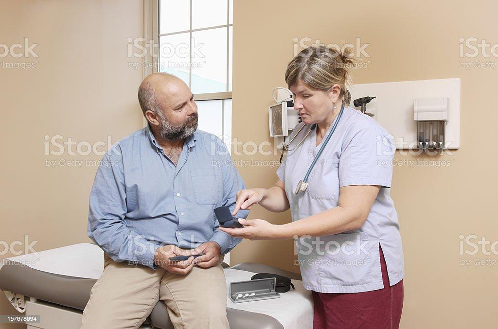 Nurse explaining the use of diabetic equipment stock photo