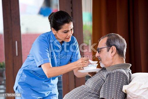 Female nurse feeding food to senior patient on bed