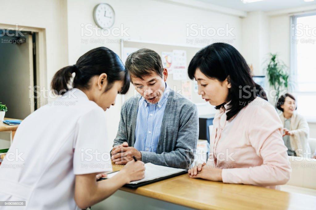 看護師の病院患者とフォームに記入 ストックフォト