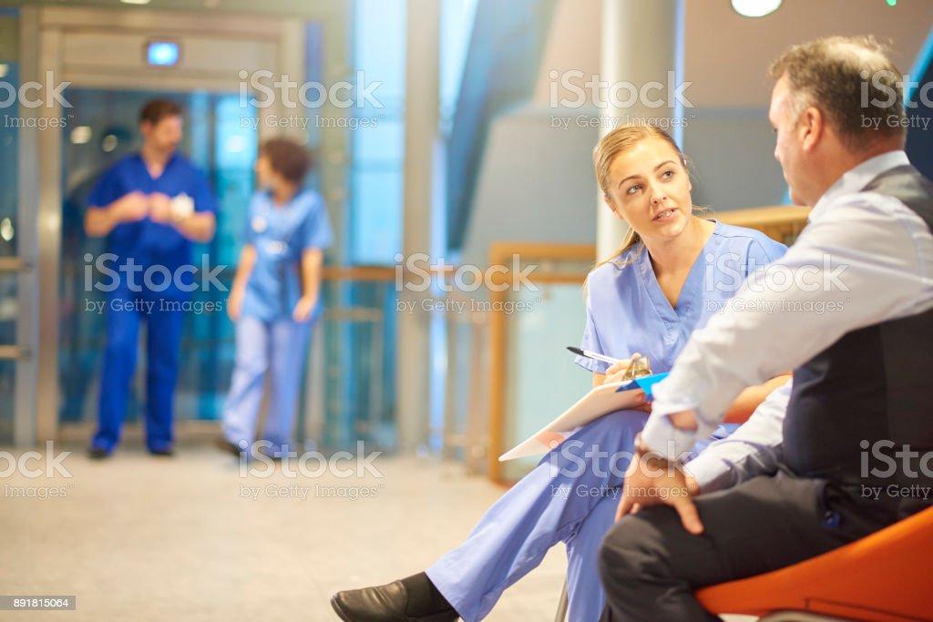 Krankenschwester ausfüllen Papierkram mit Patienten – Foto