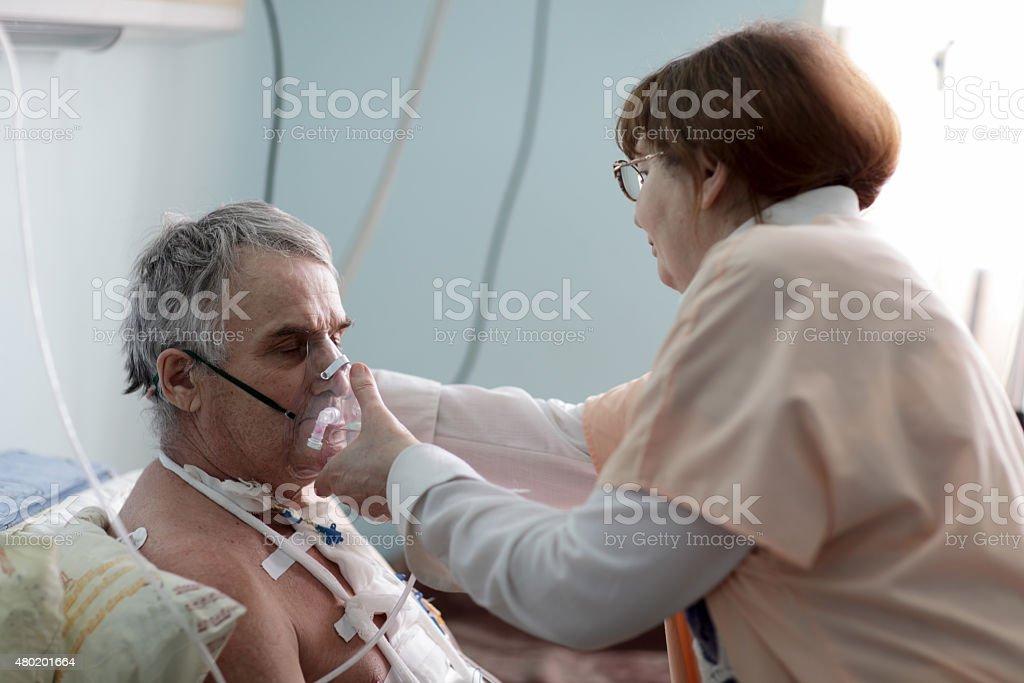 Nurse fixing oxygen mask stock photo