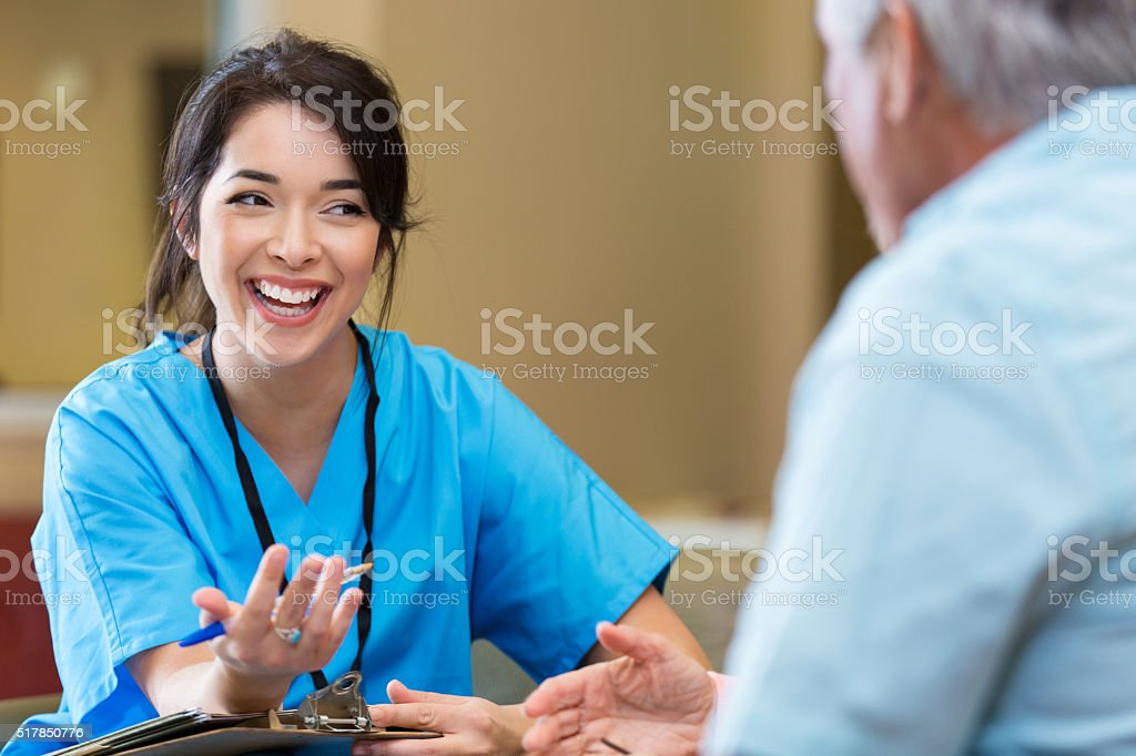 Nurse gestures as she talks with senior male patient stock photo