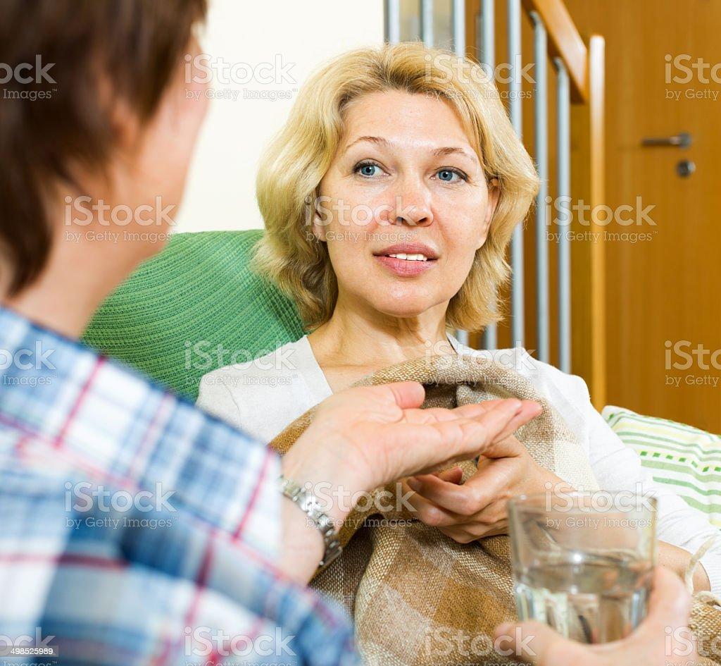 nurse gives a sleeping pill to woman stock photo