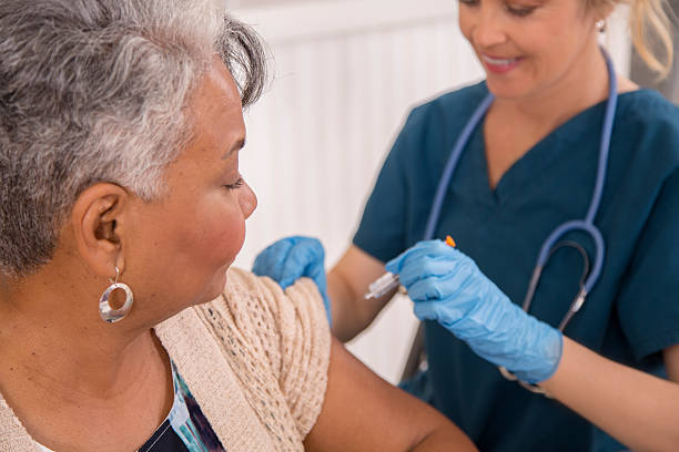 Nurse gives flu vaccine to senior adult patient at clinic. Nurse gives flu vaccine to African descent, senior adult patient at a local pharmacy, clinic, or doctor's office. flu vaccine stock pictures, royalty-free photos & images