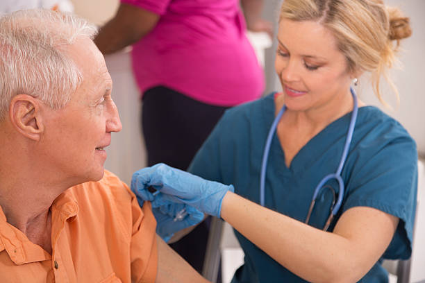 Nurse gives flu vaccine to senior adult patient at pharmacy. Nurse gives flu vaccine to senior adult male patient at a local pharmacy.  Customer in background at checkout counter. flu shot stock pictures, royalty-free photos & images