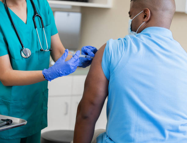 Nurse gives mature African American man a vaccination in doctor's office during coronavirus pandemic stock photo