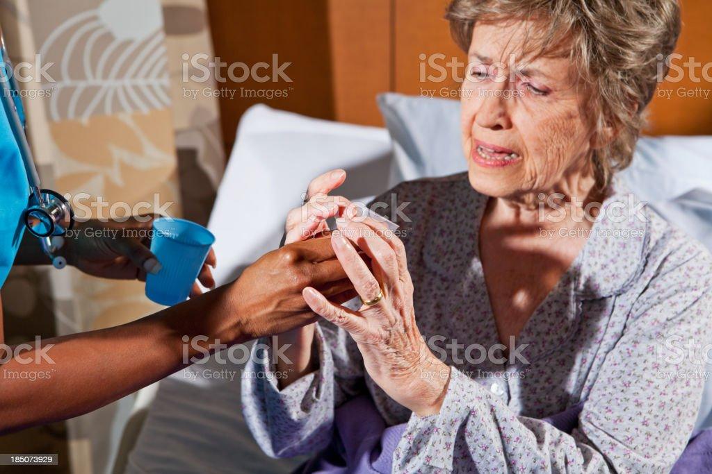 Nurse giving medication to senior woman in hospital room royalty-free stock photo