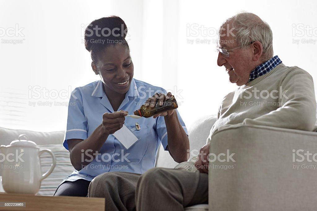 Nurse giving medicinal syrup to elderly man at home stock photo